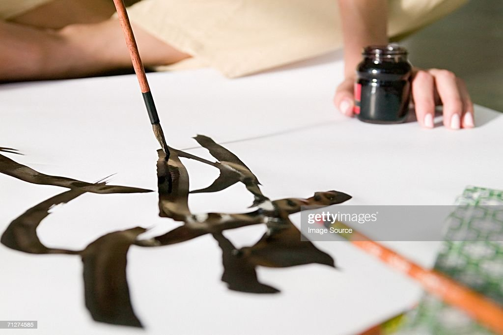 Woman painting chinese symbol : Stock Photo