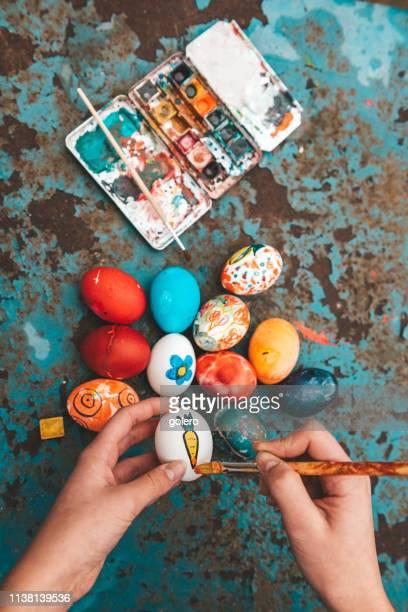 frau malt bunte ostereier - osterei stock-fotos und bilder