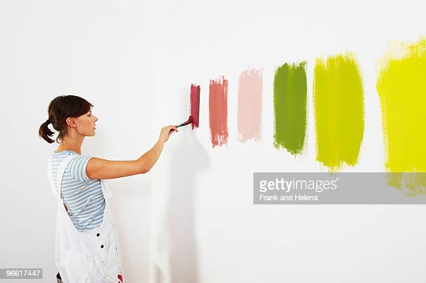 woman painting colour swatches on wall - home showcase interior stock photos and pictures