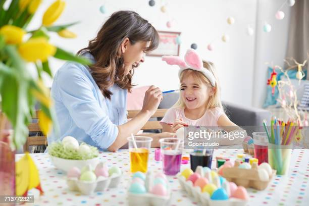 Woman painting daughters nose while painting easter eggs at table