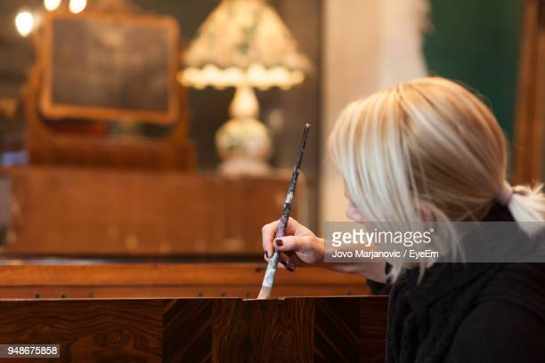 Woman Painting Furniture In Store