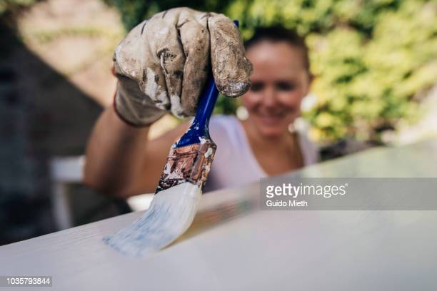 Woman painting furniture outdoor.