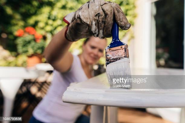 Woman painting furniture.
