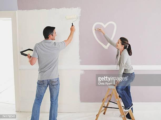 Femme peinture de cœur sur le mur avec l'Homme dans la chambre