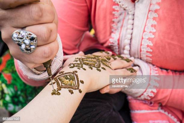 woman painting henna on the hand - moroccan culture stock photos and pictures