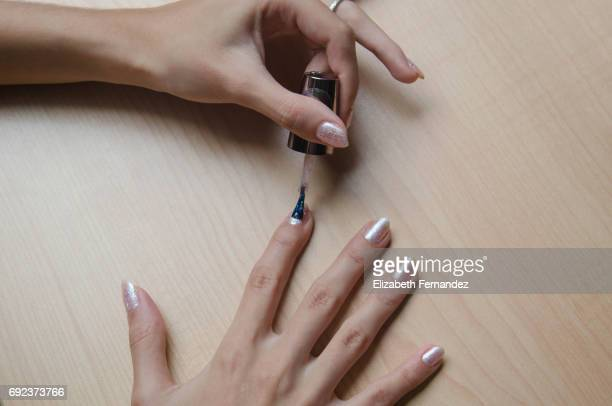 Woman painting her hails with nail polish.