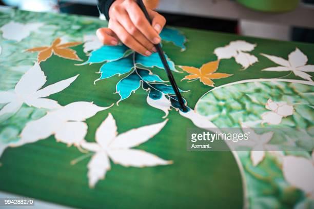 woman painting in a batik workshop - batik stock pictures, royalty-free photos & images
