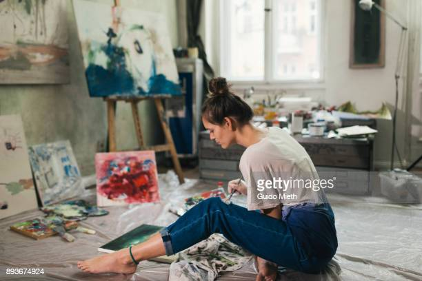 Woman painting in artist studio.