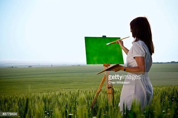 Woman painting in wheat-field, rear