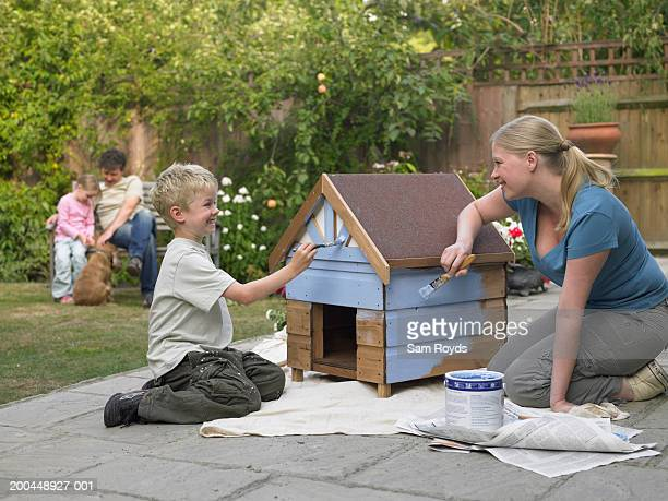 Woman painting kennel with son (6-8), in garden, smiling