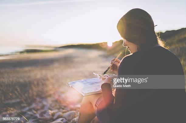 woman painting on beach - künstlerischer beruf stock-fotos und bilder