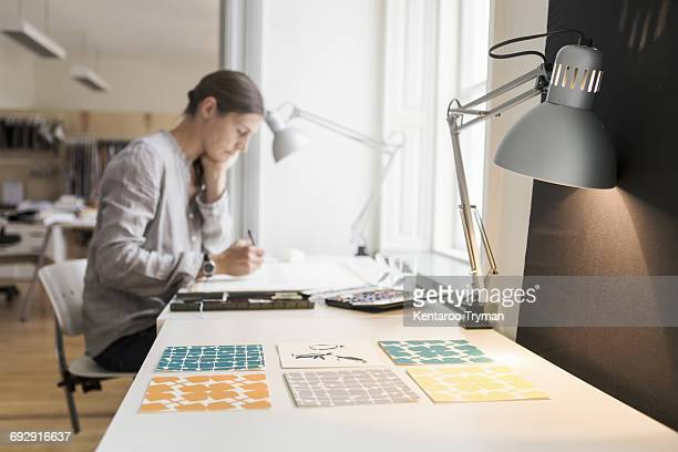 Woman painting on canvas by illuminated desk lamp at creative office