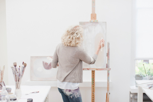 Woman painting on canvas in art studio 104821848