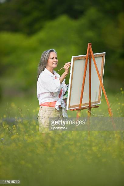 Woman Painting On Easel In Wildflower Field
