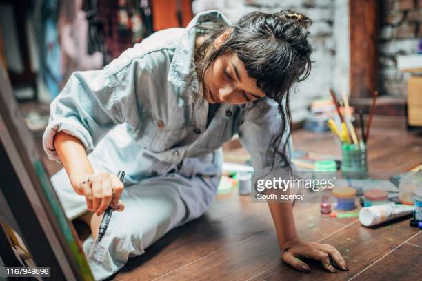woman painting on the floor at home - dipinto foto e immagini stock