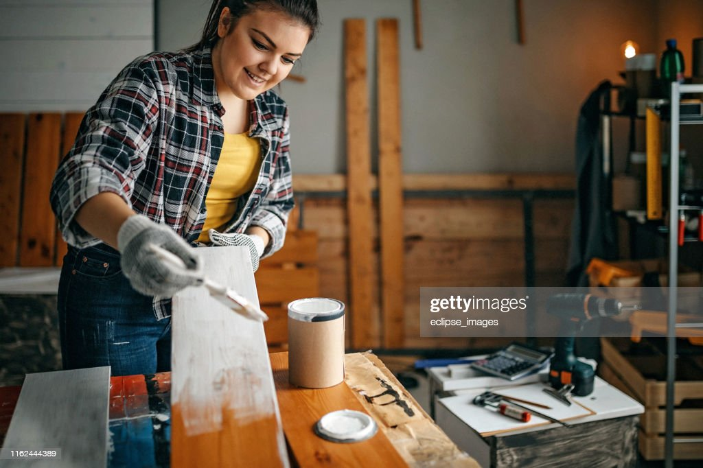 Woman painting plank in garage : Stock Photo