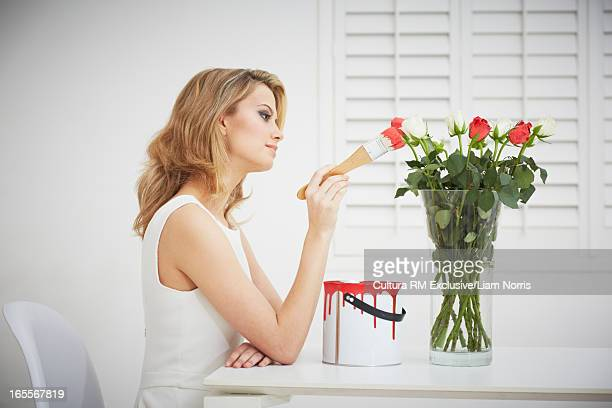 Woman painting roses red