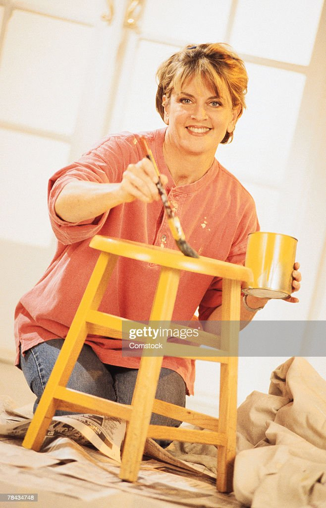 Woman painting stool at home : Stockfoto