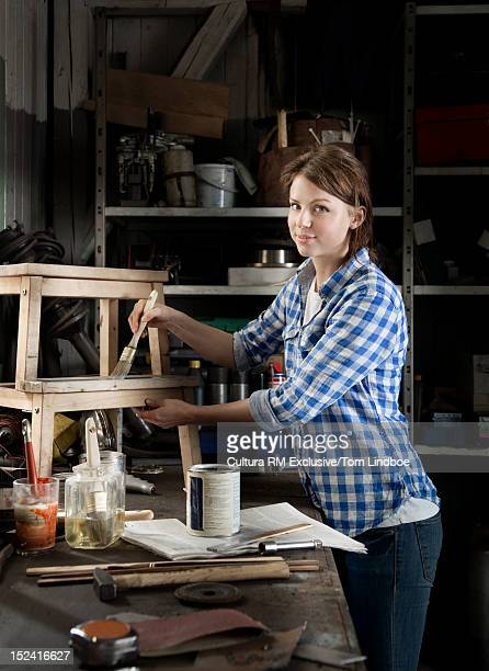 Woman painting stool in workshop