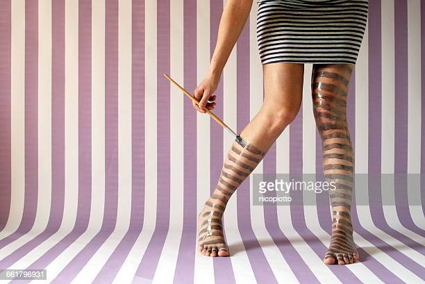 Woman painting stripes on her legs
