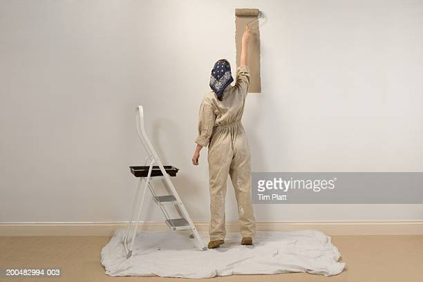 woman painting wall, rear view - step ladder stock photos and pictures