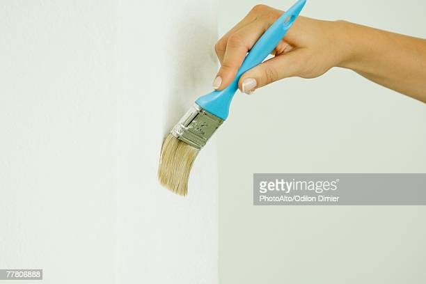 Woman painting wall with paintbrush, cropped view of hand