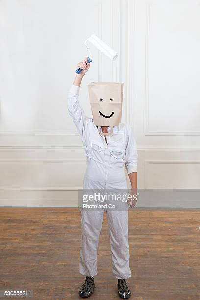 Woman painting  wearing paper bags on heads