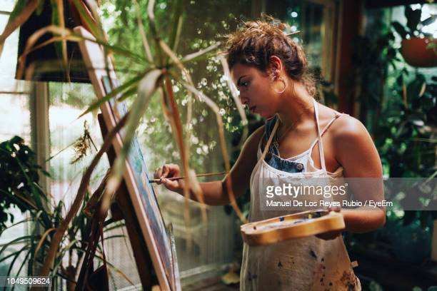 Woman Painting While Standing At Home