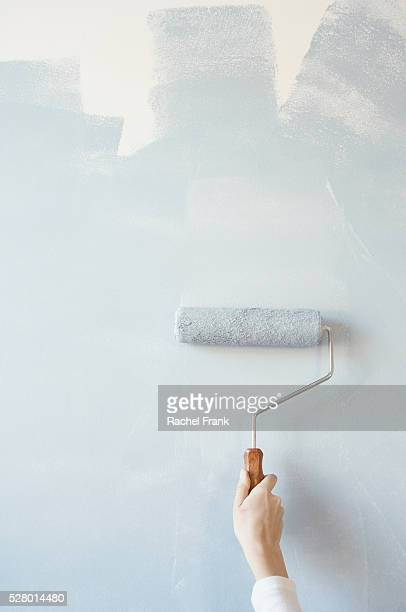 Woman painting with paint roller