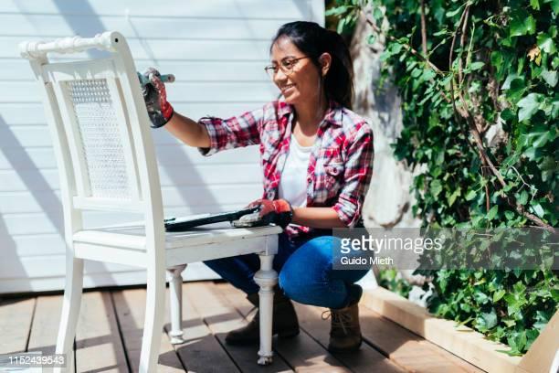 woman painting wooden chair in garden house. - herbouwen stockfoto's en -beelden