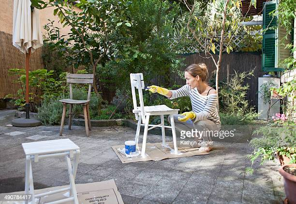 woman painting wooden chairs in garden
