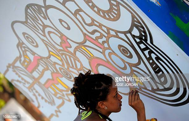 A woman paints a mural at the Rototom Sunsplash European reggae festival in Benicasim Spain on August 21 2010 The festival runs from August 2128 AFP...