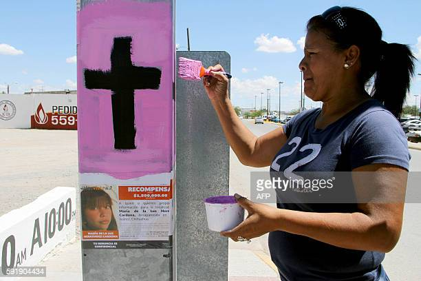 A woman paints a pink cross during the start of the 'Cruz Rosa Visibilización del Feminicidio' campaign in Ciudad Juarez Chihuahua State Mexico on...