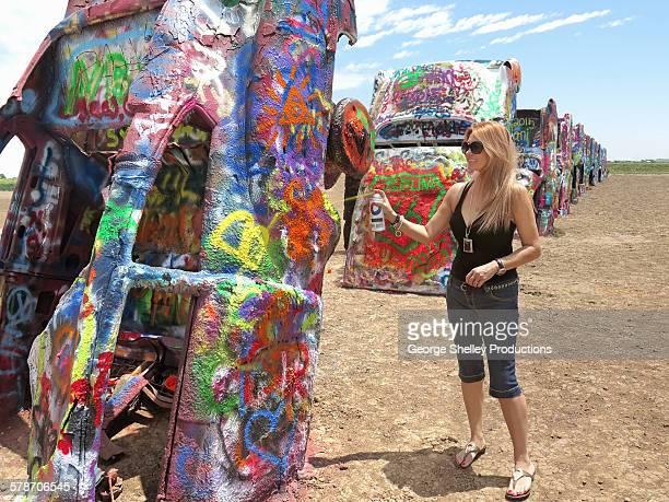 Woman paints car at Cadallac Ranch
