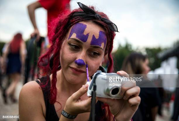 A woman paints her face in the same style as Shaggy 2 Dope from the hip hop duo Insane Clown Posse during the Juggalo March at the Lincoln Memorial...