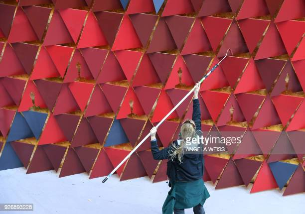 A woman paints the backdrop of the red carpet ahead of the 90th Oscars ceremony in Hollywood California on March 3 2018 / AFP PHOTO / ANGELA WEISS