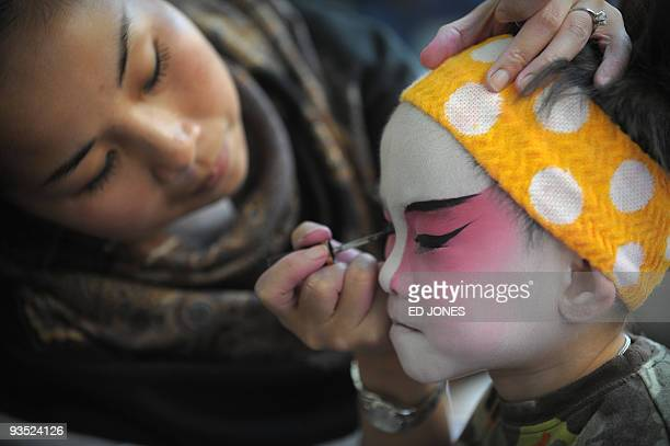A woman paints the face of a child as a traditional Chinese opera is performed nearby in Hong Kong on November 29 2009 Part of 'Cantonese Opera Day'...