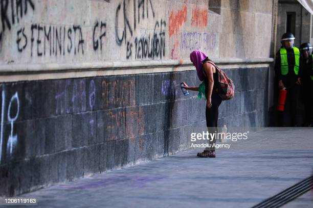 A woman paints the outside of the Palacio Nacional during a protest on the International Women's Day in Mexico City Mexico on March 8 2020