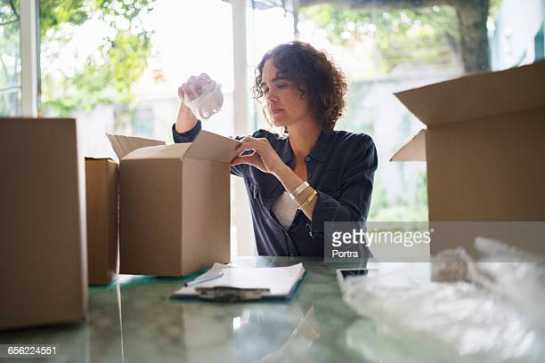Woman paking coffee cup in cardboard box at home