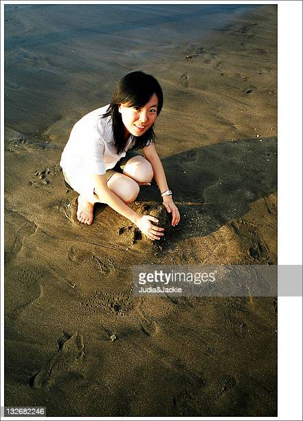 Woman palying with sand on beach