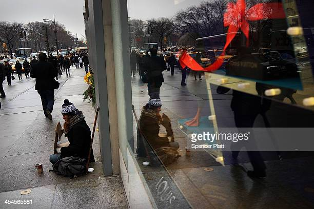 A woman panhandles in front of holiday windows along 5th Avenue on December 9 2013 in New York City With the lighting of the Rockefeller Center...