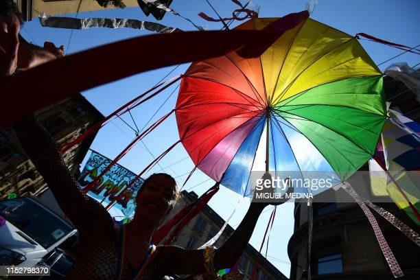 A woman parades with a rainbow umbrella during the Milan Pride 2019 on June 29 2019 in Milan as part of the LGBT Pride month marking the 50th...