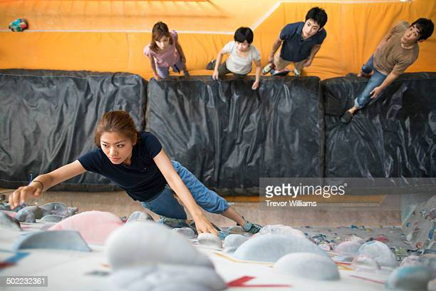 A woman partaking in a class at a bouldering gym