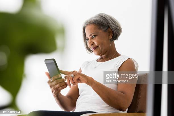 woman participates in video call with family - using phone stock pictures, royalty-free photos & images