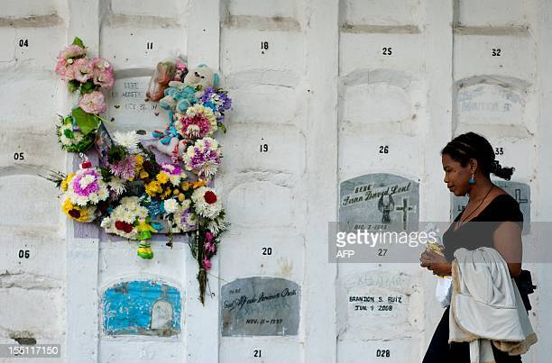 A woman pases by a grave decorated with flowers at the Central Cemetery of Cali Colombia on November 1 during the All Saints Day celebrations AFP...