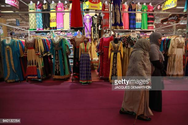 Woman pass a booth selling clothing during the 35th annual meeting of the French Muslim community on March 30 2018 at Le Bourget north of Paris / AFP...