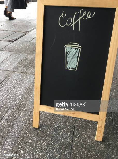 Woman Pass by a Coffee Sign
