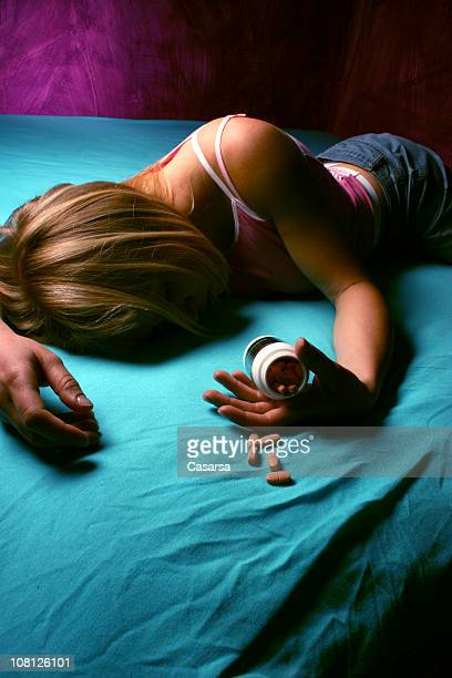 mujer pasado en la cama y mantener el recipiente de píldoras - suicidio pastillas fotografías e imágenes de stock