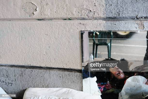 A woman passed out on heroin is reflected in a mirror under a bridge where she lives with other addicts in the Kensington section which has become a...