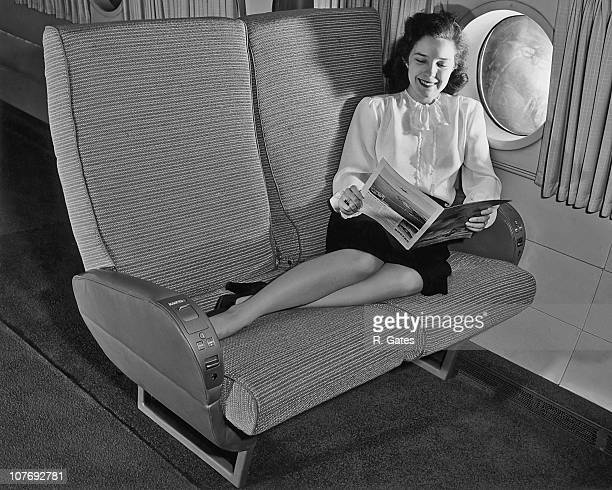 A woman passenger reads a magazine on board a Boeing airliner circa 1955